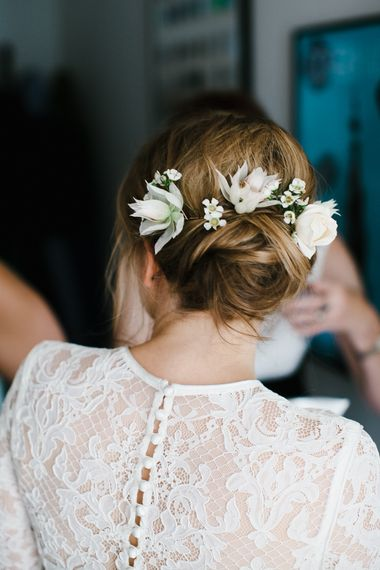 Pinned bridal up do with fresh flower in her hair
