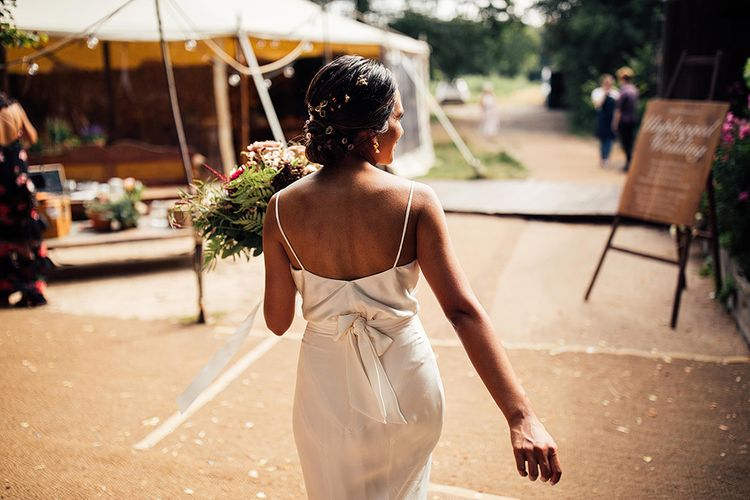 Bride in strappy dress with bridal updo and flowers