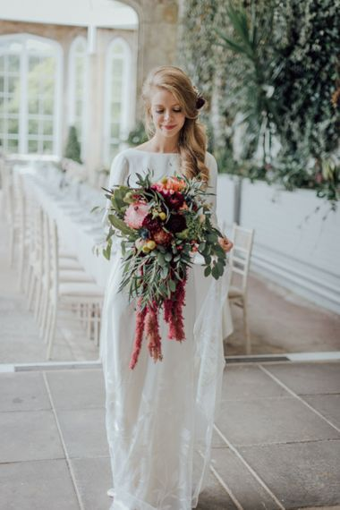 Bride with trailing side ponytail and fresh flowers in her hair