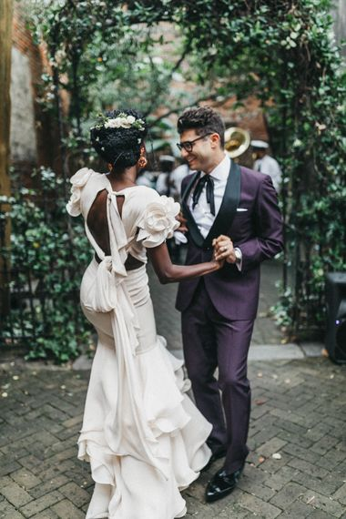 Black bride in second hand wedding dress with braided up do and fresh flowers