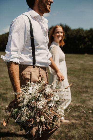 新郎站在背带上,手持一束野花结婚花束
