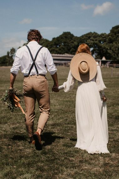 Boho bride and groom holding hands at Wickerwood Farm