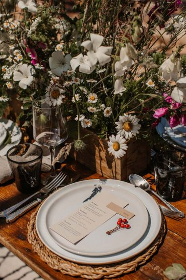Place setting with wicker place mat and wildflower centrepieces