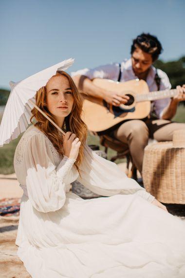 新娘穿着长袖婚纱,手持雨伞