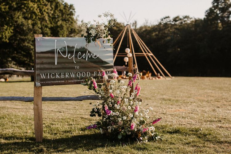 Wickerwood Farm wedding venue sign decorated with flowers