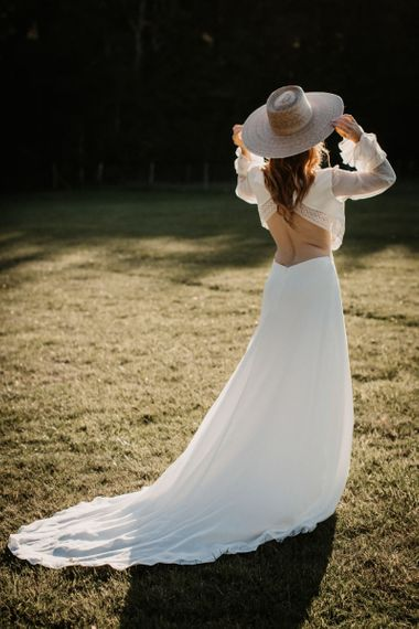 Boho bride in backless wedding dress and straw hat