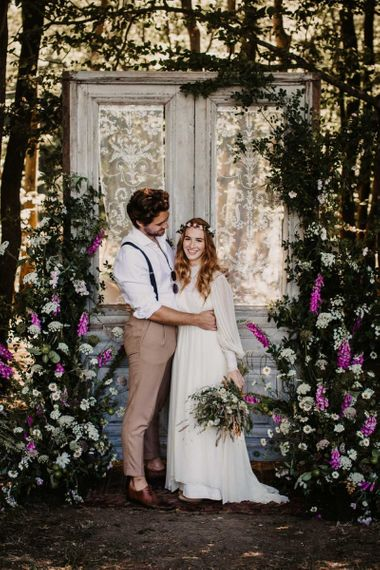 Bride and groom portrait at Wickerwood Farm with door and wildflower backdrop