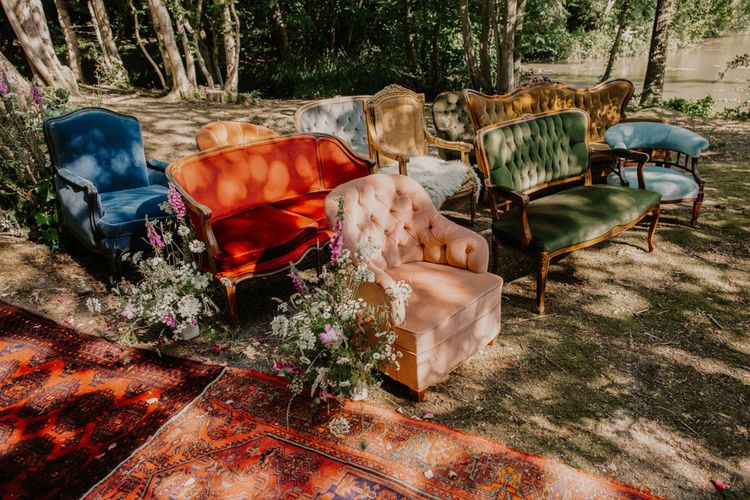 Vintage chairs and sofas at outdoor woodland wedding ceremony