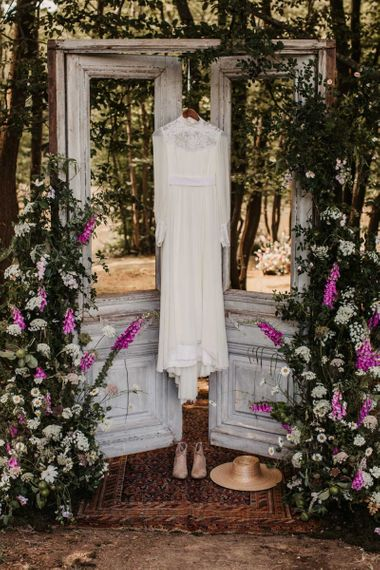 Boho wedding dress with high neck and long sleeves hanging up on wooden doors