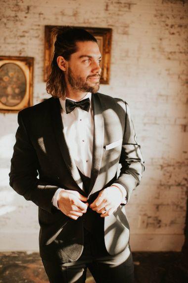 Groom in black tie suit