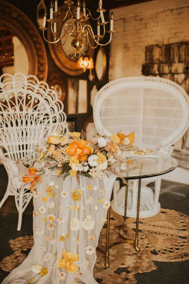 Sweetheart table with peacock chairs and orange bridal bouquet