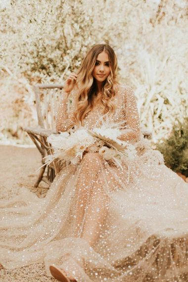 Boho bride in sparkly wedding dress with wavy hair and dried flower bouquet