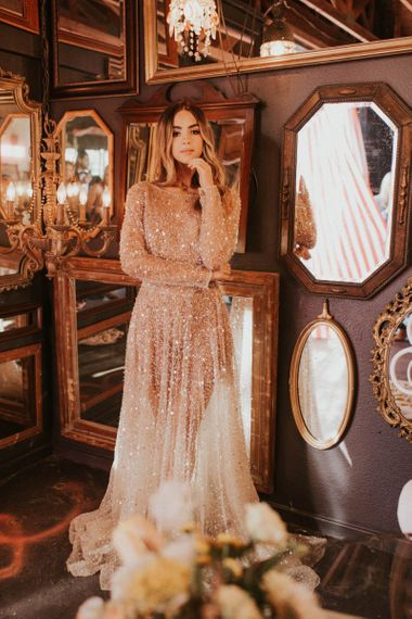Boho bride in sparkly wedding dress standing in front of ornate mirrors