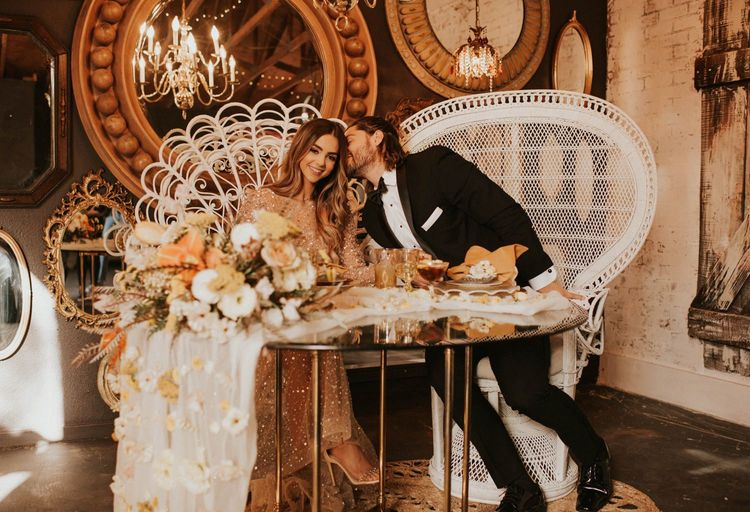 Bride and groom sitting at sweetheart table in peacock chairs