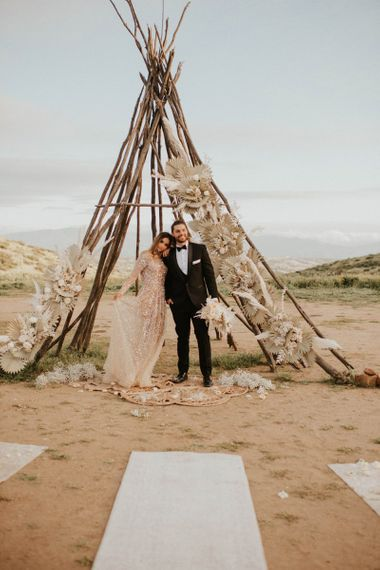 Naked tipi decorated with dried palm leaves and grasses