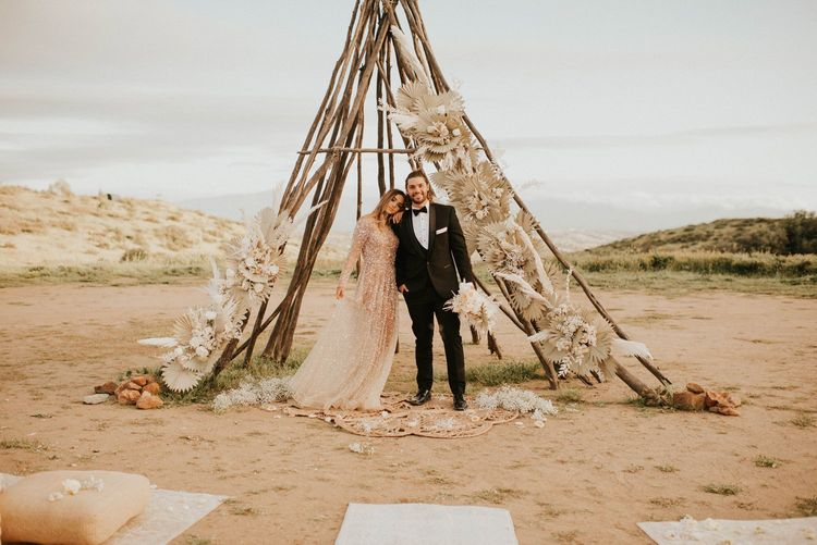 Boho bride and groom standing in from of a naked tipi structure