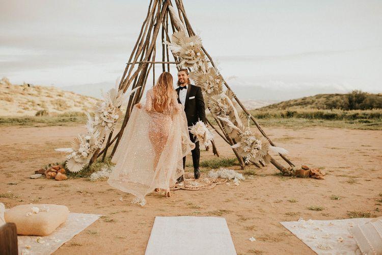 Boho bride in sparkly wedding dress swinging the skirt
