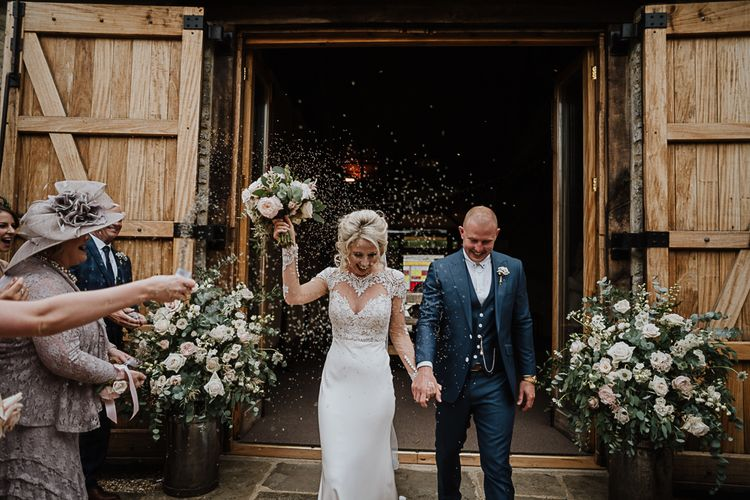 Confetti Moment | Bride in Lace Martina Liana Wedding Dress with Long Sleeves | Groom in Blue Moss Bros. Suit | Fairylight Tythe Barn Wedding with Dreamcatchers | New Forest Studio Photography