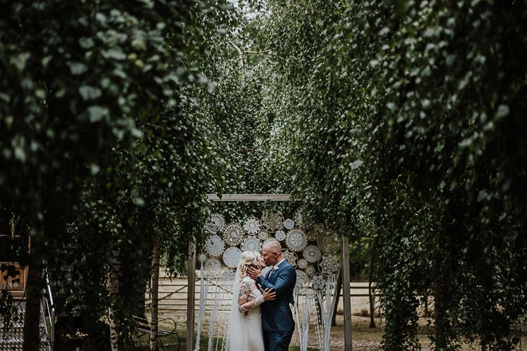 Dreamcatchers | Bride in Lace Martina Liana Wedding Dress with Long Sleeves | Groom in Blue Moss Bros. Suit | Fairylight Tythe Barn Wedding with Dreamcatchers | New Forest Studio Photography