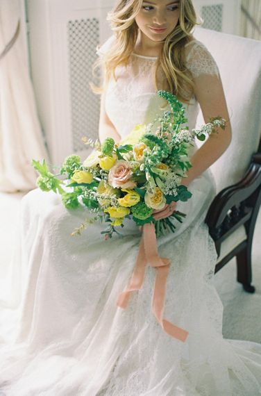 Bride in Naomi Neoh Wedding Dress with Yellow and Green Bouquet Tied with Ribbons