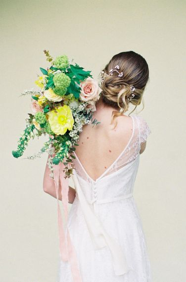 Bride in Naomi Neoh Wedding Dress Holding a Yellow and Green Bridal Bouquet Over Her Shoulder