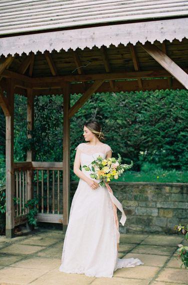 Bride in Naomi Neoh Wedding Dress Holding a Yellow & Green Wedding Bouquet