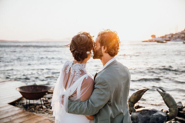 Groom kisses bride in wedding capelet at Mykonos wedding
