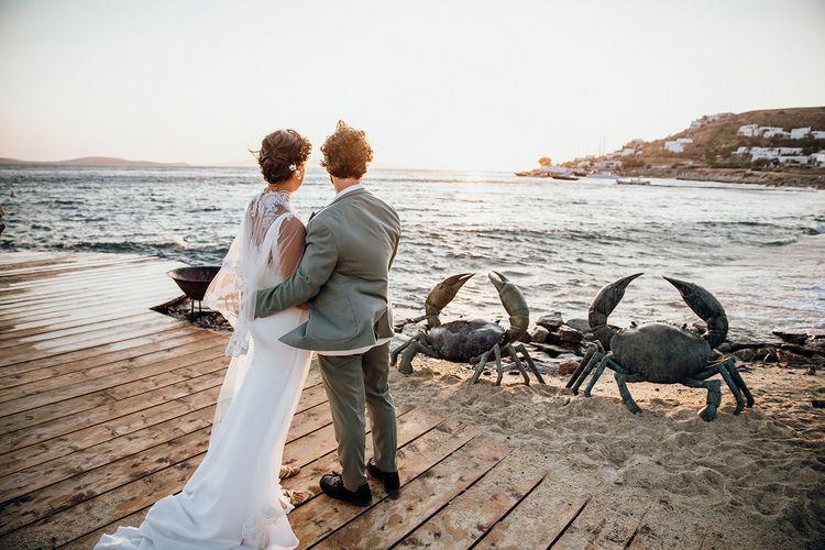 Bride in wedding capelet with groom overlooking the beautiful views at Mykonos wedding