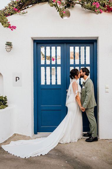 Bride in wedding capelet kisses new husband