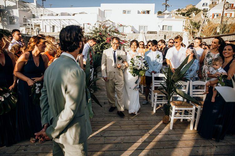 Bride walks down the aisle to meet groom