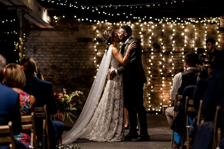 Bride in Grace Loves Lace Rosa wedding dress kissing her groom at the fairy light altar