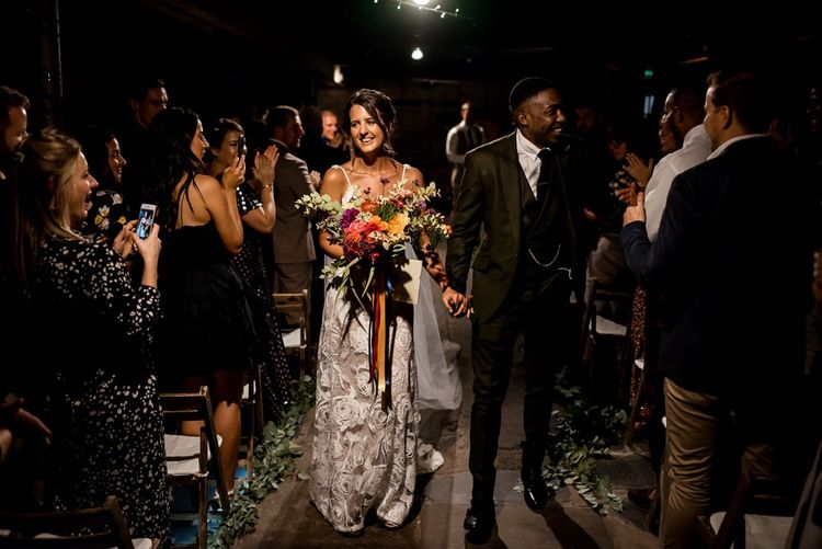 Bride in Grace Loves Lace Rosa wedding dress walking up the aisle with her husband
