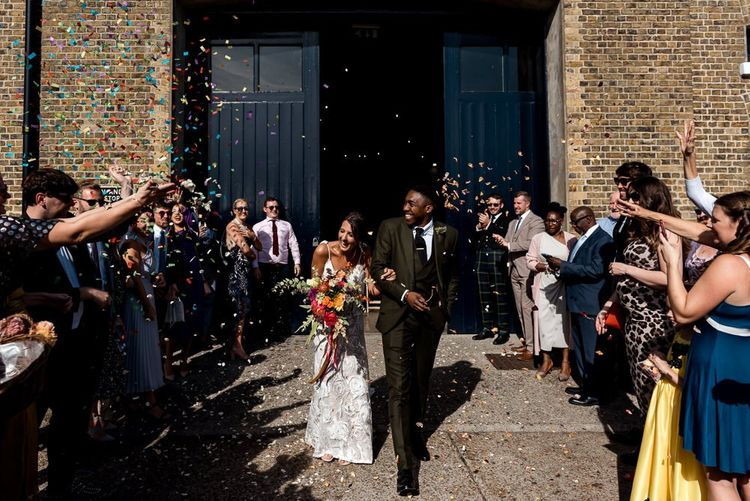 Confetti exit at Trinity buoy Wharf with Bride in Grace Loves Lace Rosa wedding dress and groom in Hackett London suit
