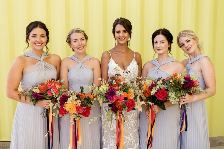 Bridal party portrait with bridesmaids in grey halter neck dresses and bride in Grace Loves Lace Rosa wedding dress
