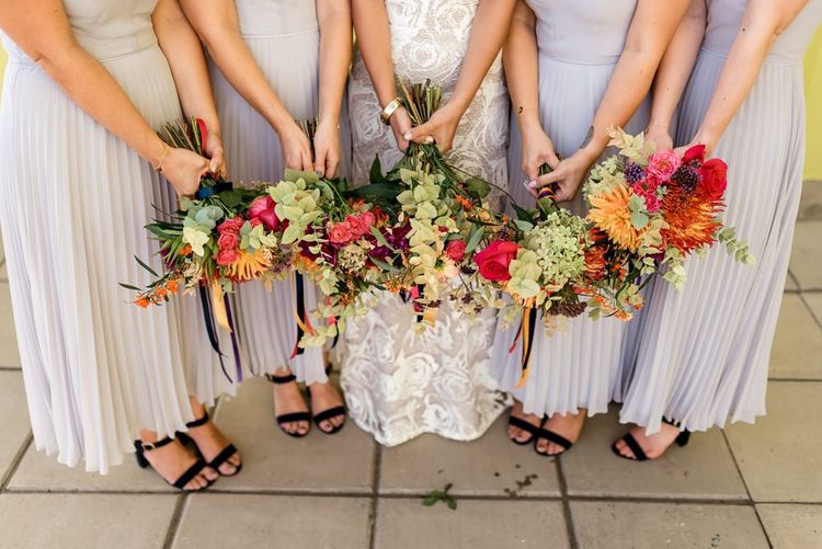 Colourful wedding bouquets and bride in Grace Loves Lace wedding dress