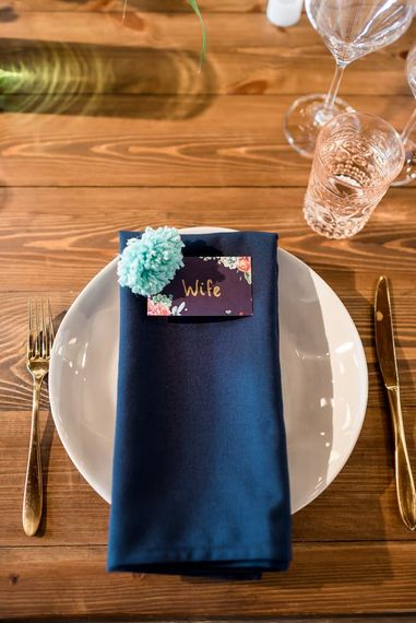 Place setting with navy napkin, floral name place card and pompom