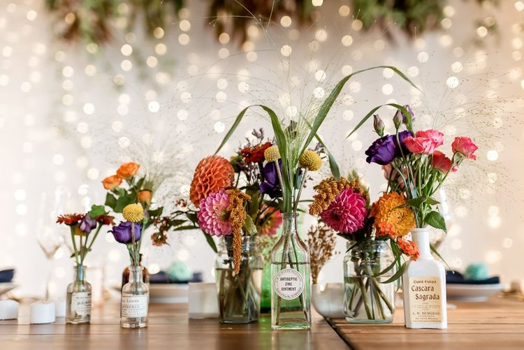 Colourful dahlias and flower stems in bottles