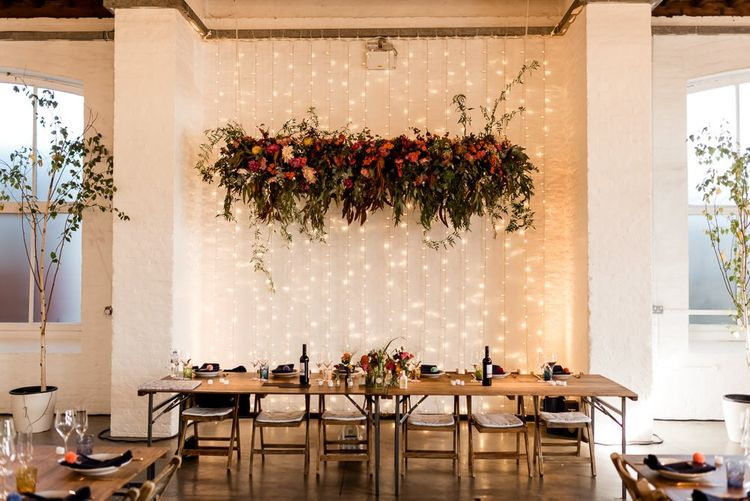 Top table with fairy light back drop and flower installation