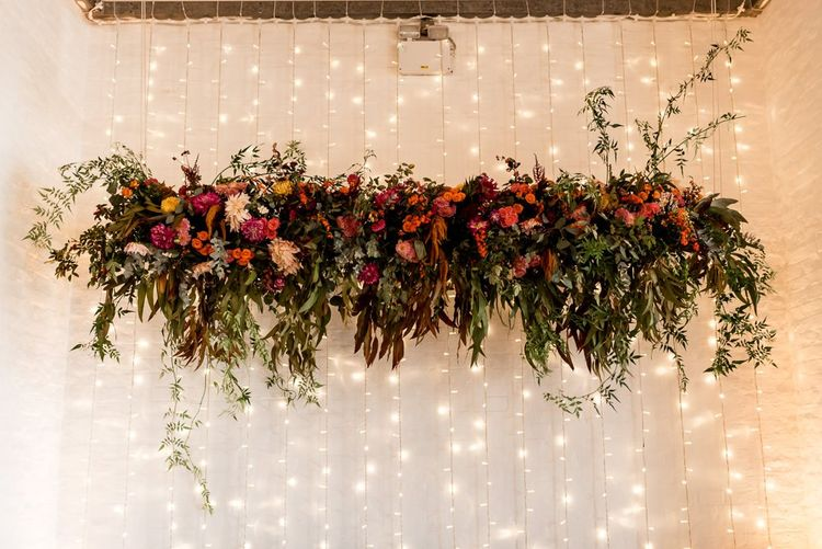 Colourful floral installation for wedding with bride in Grace Loves Lace Rosa bridal gown