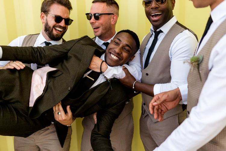 Groomsmen in check suits holding the groom