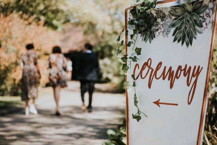 Ceremony Sign in Copper Frame with Trailing Ivy | Peacock Chairs, Sweetheart Table and Leather Jackets for Autumn Wedding at The Copse |  Rosie Kelly Photography