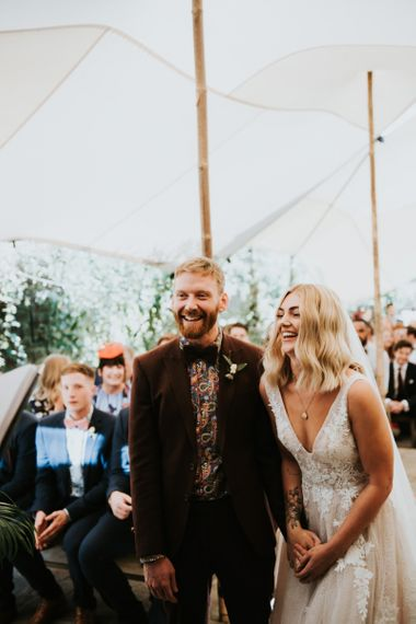 Bride in Katia Dress by Novia D'Art with V-Neck, Plunge Back and Embroidered Lace Overlay | Groom in Brown Two-Piece Gresham Blake Suit with Bow Tie and Patterned Shirt from Pretty Green | Wedding Ceremony Under Stretch Tent at The Copse | Peacock Chairs, Sweetheart Table and Leather Jackets for Autumn Wedding at The Copse |  Rosie Kelly Photography