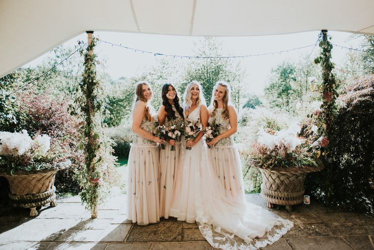 Bride in Katia Dress by Novia D'Art with V-Neck, Plunge Back and Embroidered Lace Overlay | Bridesmaids in Blush Drop Waist Dresses with Embroidered Flowers by ASOS | Bouquets of Dusty Pink and Burgundy Flowers with Foliage | Peacock Chairs, Sweetheart Table and Leather Jackets for Autumn Wedding at The Copse |  Rosie Kelly Photography