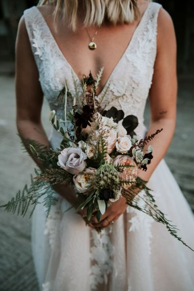 Bride in Katia Dress by Novia D'Art with V-Neck, Plunge Back and Embroidered Lace Overlay | Bridal Bouquet of Dusty Pink and Burgundy Flowers with Foliage | Peacock Chairs, Sweetheart Table and Leather Jackets for Autumn Wedding at The Copse |  Rosie Kelly Photography