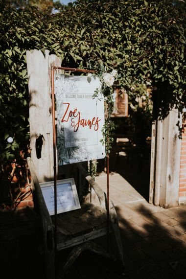 Wedding Welcome Sign in Freestanding Copper Frame | Peacock Chairs, Sweetheart Table and Leather Jackets for Autumn Wedding at The Copse | Rosie Kelly Photography
