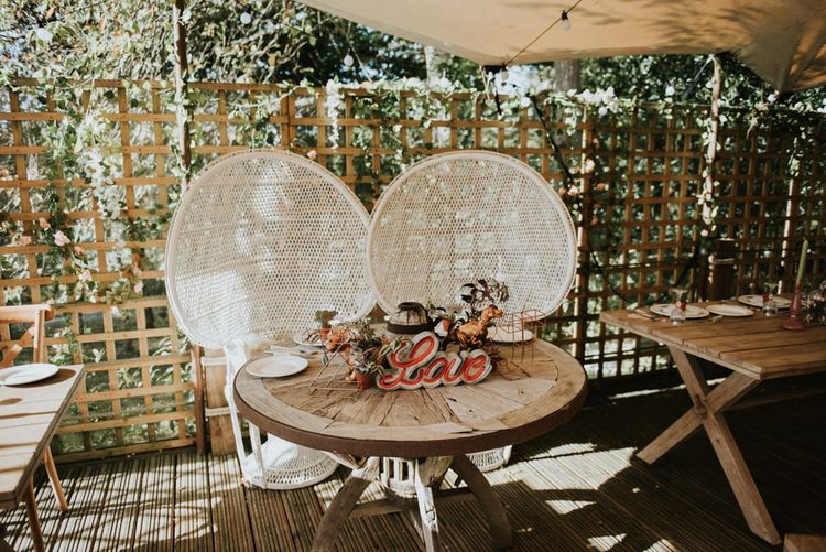 White Peacock Chairs for Wedding Breakfast | Round Wooden Sweetheart Table | Copper Metal Initial Letters | Potted Succulents | Wooden Love Sign | Peacock Chairs, Sweetheart Table and Leather Jackets for Autumn Wedding at The Copse | Rosie Kelly Photography