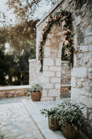 Pink wedding flower arch at ceremony venue
