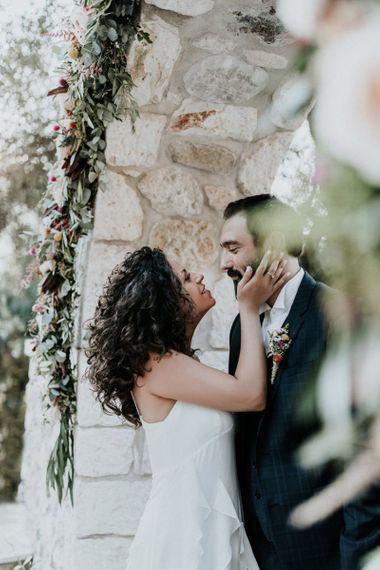 Bride in Max Mara dress kissing groom