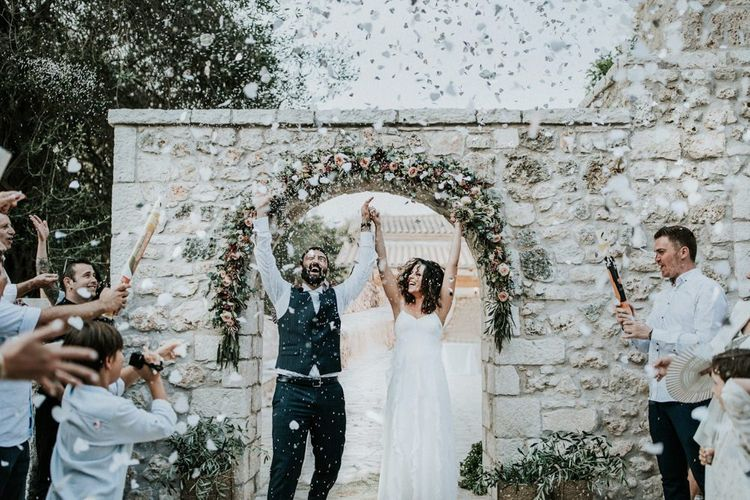 Confetti exit for bride in Max Mara wedding dress and groom