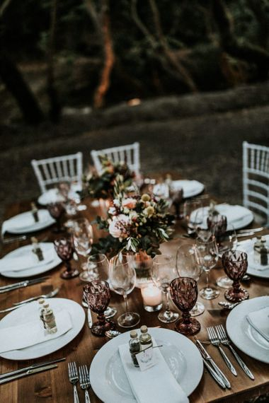 Wedding table decor with flowers and purple glassware